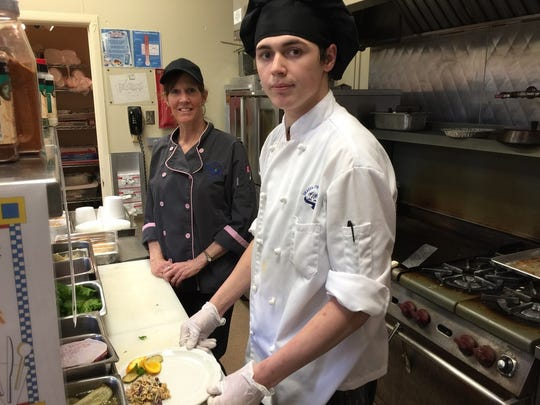 Student Seth Koeller with an instructor in the kitchen at The Classroom restaurant.