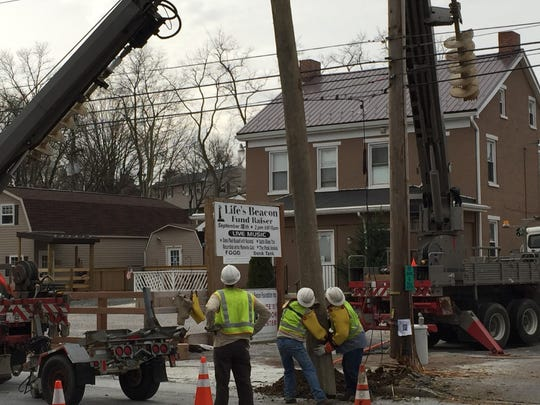 Met-Ed workers replace a pole sheared by a careening truck on Tuesday in York.