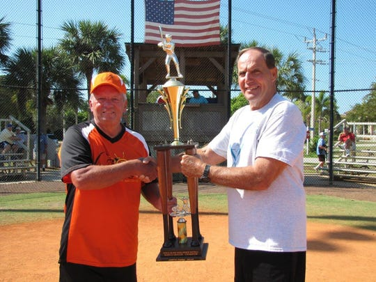 Manager Mike Arnold is presented the Marco Division Championship Trophy by League Commissioner Bill Shurina.