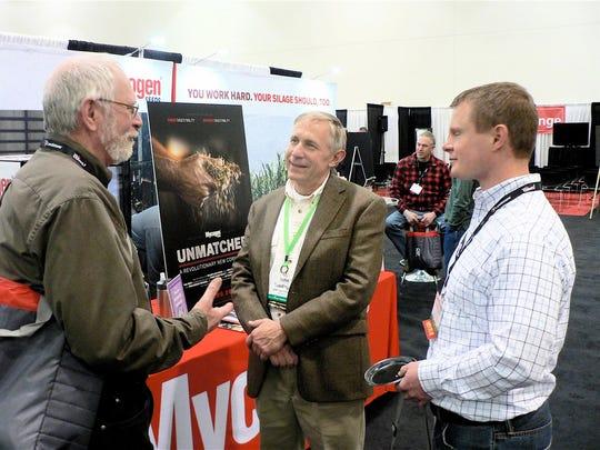 John Ruedinger of Ruedinger Farms (center),  Van Dyne, listens at the Mycogen exhibit.
