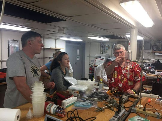 Cape Henlopen High School Teacher Bill Geppert, UDel Graduate Student Julia Guimond look on as George Luther explain how to use a piece of equipment on the RV Atlantis.