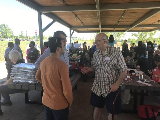 David Jones (right), a Shady Grove Presbyterian member, talks with Nauman Khalim during Sunday's picnic.