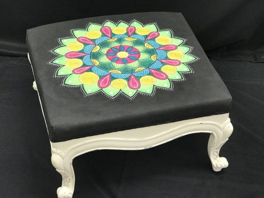 A hand-painted ottoman available at the Upcycle Auction.