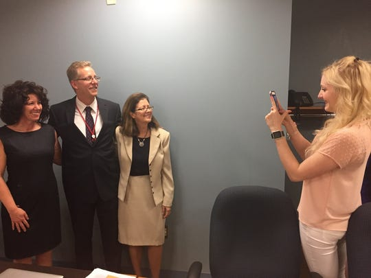Hope Abrom, daughter of Lebanon School District's superintendent, Arthur Abrom, takes a photo of her father as he poses with Lebanon Mayor Sherry Capello and outgoing Superintendent Marianne Bartley, who is retiring in June.