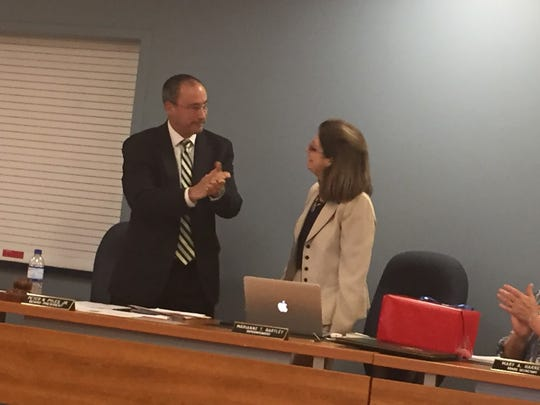 Lebanon School Board President Peter Pyles leads others in a standing ovation for Superintendent Marianne Bartley, who is retiring at the end of June.