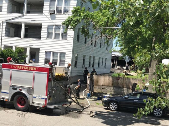 Paterson firemen remain busy at the scene following a fire in the garage behind this 20-family rental building at 81 Alabama Ave.