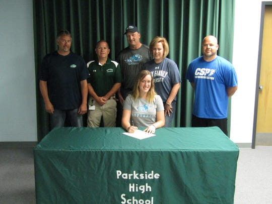 Surrounded by coaches and family, Taylor Nichols signs