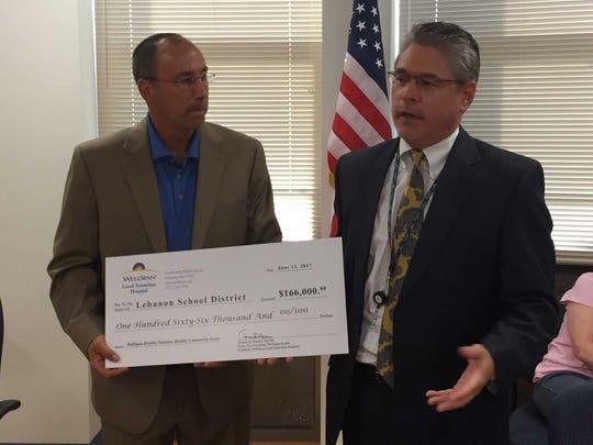 Tom Harlow (R), president of Wellspan Good Samaritan Hospital, presents a check for $166,000 to Lebanon school board President Peter Pyles.
