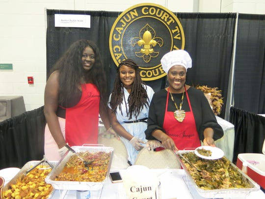Attorney Jackie Scott presided at her Cajun Court TV Booth and stirring up food were: Lawryn Scott, Asia Zovan and Scott.