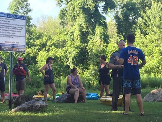 A state trooper questions of the men who were rescued while kayaking on the Swatara Creek in Jonestown Saturday afternoon.