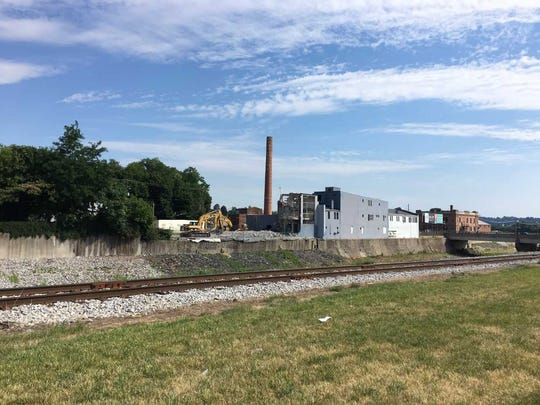The Pensupreme building on Codorus Creek's north bank is disappearing from the back to its front.