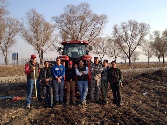 Jenny Cui's farm team poses for a photo next to their