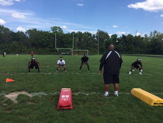 Arlington coach Steve Moorman works with linebackers.