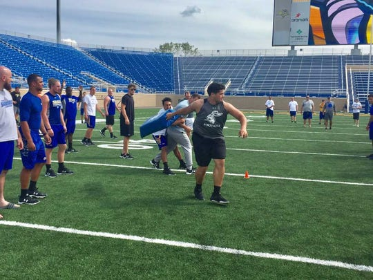 Tiano Pupungatoa, shown here throwing a tackling dummy during 'Jackrabbit Olympics' is one of the most well-liked players on the SDSU offense.