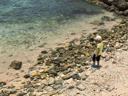 A young tourist boy approaches the water's edge at