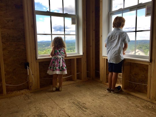Siblings Isabella and Gavin Schumacher look out the windows of a home under construction at Sleight Farm at LaGrange.