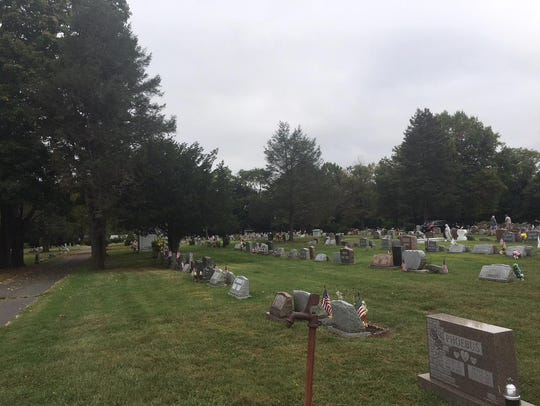 Flags can be seen on graves at Mount Holly Cemetery
