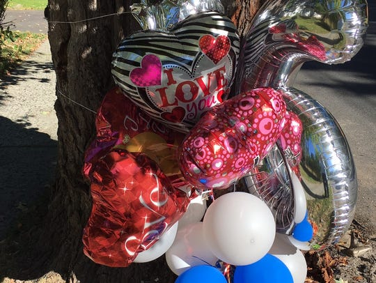 Balloons fill a memorial set up for a Plainfield man