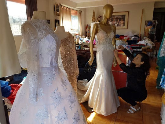 Rhodora Paloma, a local seamstress, putting the finishing touches on a gown. Paloma makes many of the dresses used by local pageant contestants.