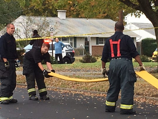 Edison firefighters work to roll up a hose following