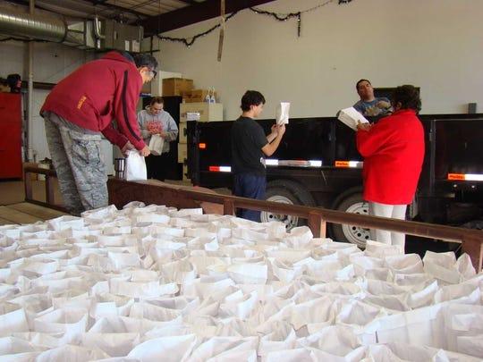 Simon Beltran, (far back atop the truck), Ronnie Beltran, Brittney LaMay, Carlos Almaraz and Beatrice Beltran help fill sacks for the annual luminaria display in Carizozo.