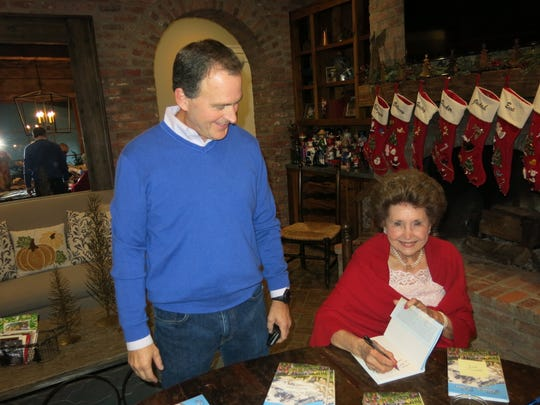 Author Anne Wilson signs a copy of her latest book,