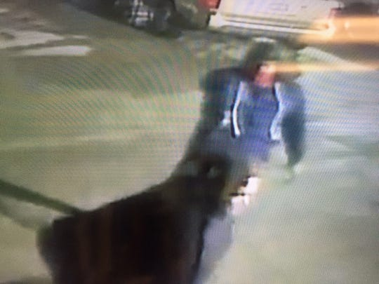 A black man wearing a dark blue hoodie and a red bandanna is suspected of robbing a victim outside of a bar on Orchard Park Drive on the night of Monday, January 9, 2018.