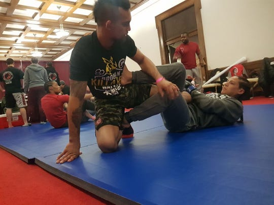 Brogan Walker Sanchez, right, gets some last-minute moves on the mat with her husband Mike Sanchez before her bout against Cheri Muraski at Invicta FC 27 in Kansas City, MO.