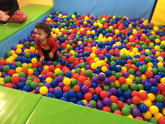 A child plays in the balls in the Tiny Tykes Town at