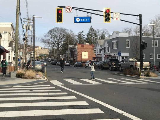 A woman crosses Millburn Avenue at the intersection
