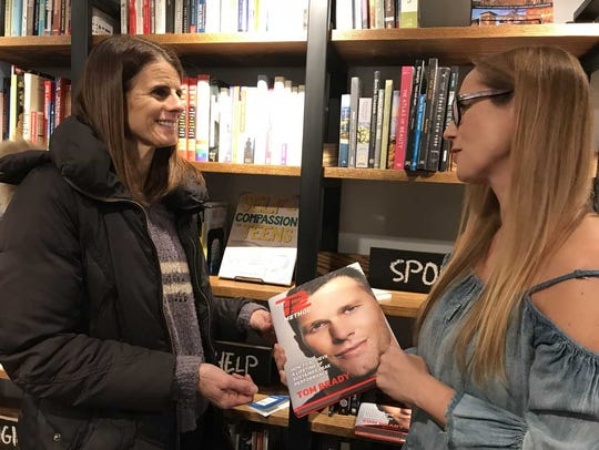 Debbie Mayo, left, and Joanna Parker-Lentz skim through a book about New England Patriots quarterback Tom Brady in The Book House in Millburn.