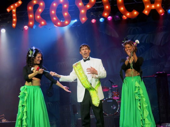 Krewe Justinian Captain Larry Pettiette is flanked by  Tropicana Dancers, of Dallas, as he makes a presentation at Krewe Justinian Grand Bal.