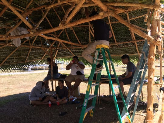 Members of the Chuukese Student Organization take a break from weaving their huts.