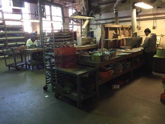 Workers at Bergamot Brass Works Inc. make brass belt