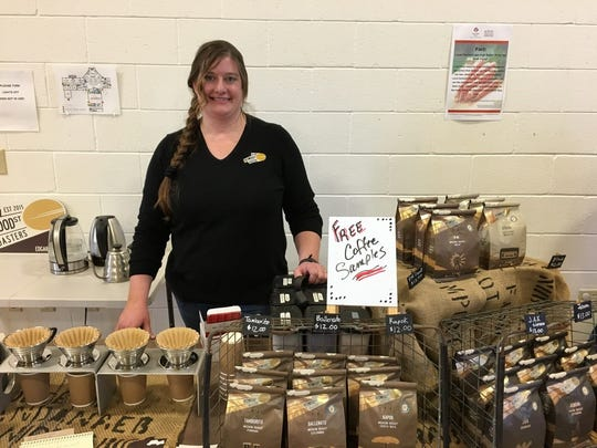 Amber Haemer, owner of Redwood Roasters, stands behind her table featuring free samples of coffee and their products.