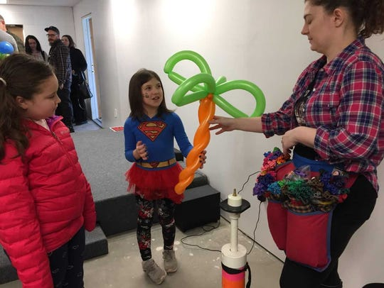Balloon artist Ashley Miller hands a palm tree to 7-year-old
