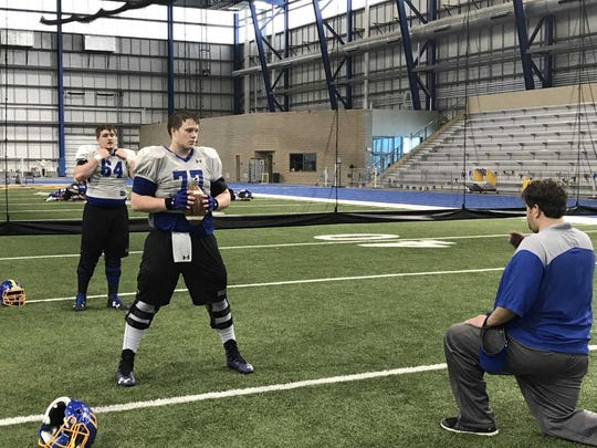 Wes Genant (77) works with offensive line coach Jason