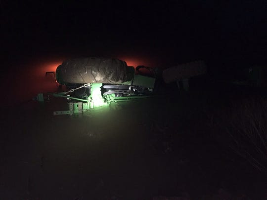 Eldon Cooper's John Deere tractor in the water on the night he was rescued when he became trapped inside the cab underwater. The tractor's emergency flashers light up the water.