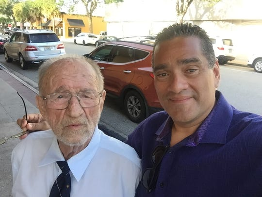 Journalist John A. Torres (R) takes a selfie with retired