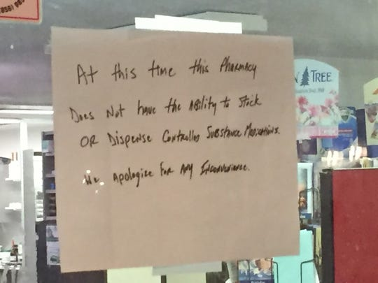 A sign on the door at Olde Medford Pharmacy notes the store no longer offers controlled substances after the November 2916 arrests of two pharmacists.