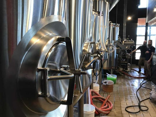 Eric Bioce and Kyle Paxton clean the brewery space at Iron Hill Brewery and Restaurant. The eatery and taproom open the week of May 1.
