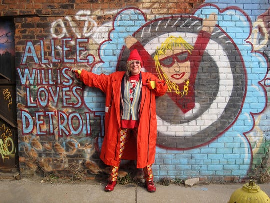 Songwriter Allee Willis poses in front of a mural of