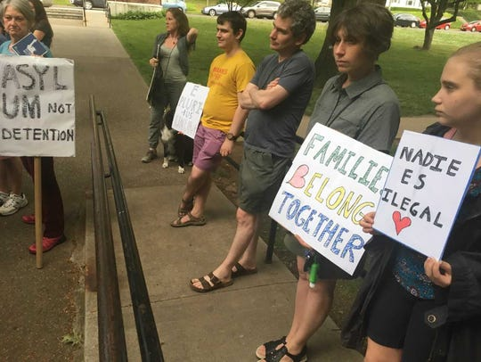 """Several people held signs, many of which said """"Families"""