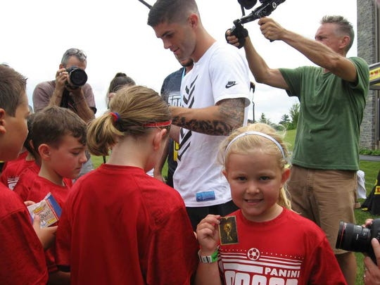 Taylor Blouch of Lebanon proudly displays the golden World Cup trading sticker given to her by Christian Pulisic Thursday during a soccer clinic in Hershey last summer.
