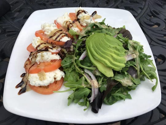 Summer tomato salad with truffle ricotta, arugula, Grainger County tomatoes, sliced red onions, avocado and a white balsamic vinaigrette.
