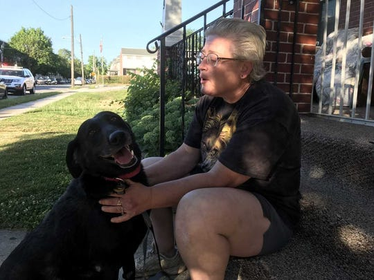 Andrea Roth pets her hero, her 13-year-old black lab, Onyx, who woke her to a fire in the garage of her Pennsylvania Avenue home.