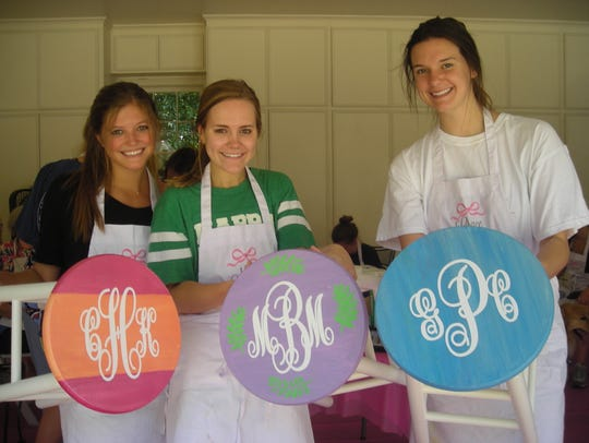 Demoiselle Debs Catherine Humphrey, Molly Bowman, Grace Poimboeuf spent the morning painting stools used at the December Demoiselle Ball.