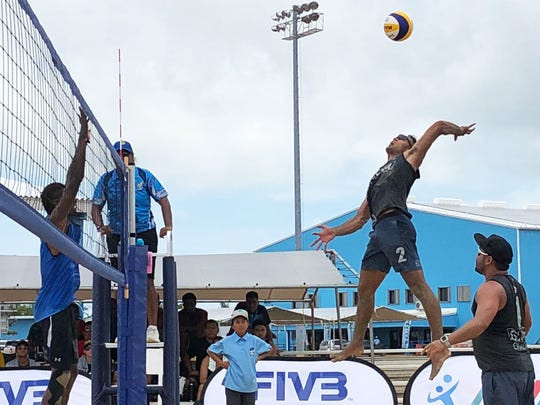 Guam's Ryan Eugenio goes airborne to rip a shot over a Palauan blocker while partner Shintaro Okada, below, awaits the outcome. Palau beat Guam in straight sets and Guam was scheduled to play for the bronze as of press time.