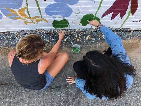 Downtown Henderson Partnership Executive Director Lindsay Locasto, left, and Ohio Valley Art League Executive Director Jordyn Myracle apply green paint to represent cacti on the mural in the 200 block of Second Street beside The Perch.