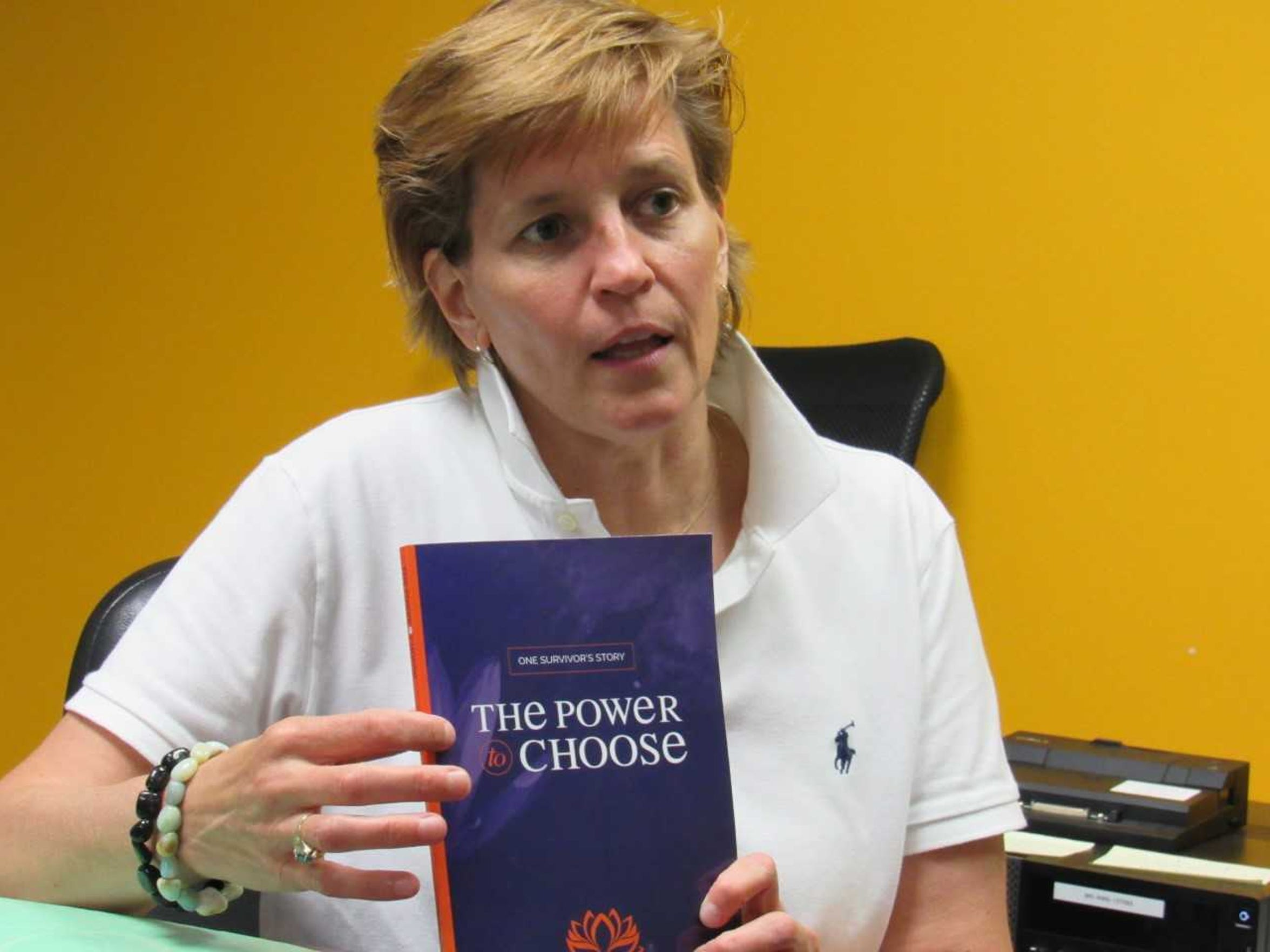 Susan Bisaha posing with her book, which details her accounts of sexual abuse growing up.